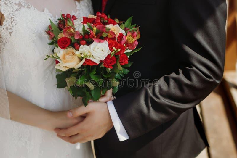 Γαμήλια ανθοδέσμη των κόκκινων ορχιδεών τριαντάφυλλων μοντέρνο αγκάλιασμα γαμήλιων ζευγών στοκ εικόνες με δικαίωμα ελεύθερης χρήσης