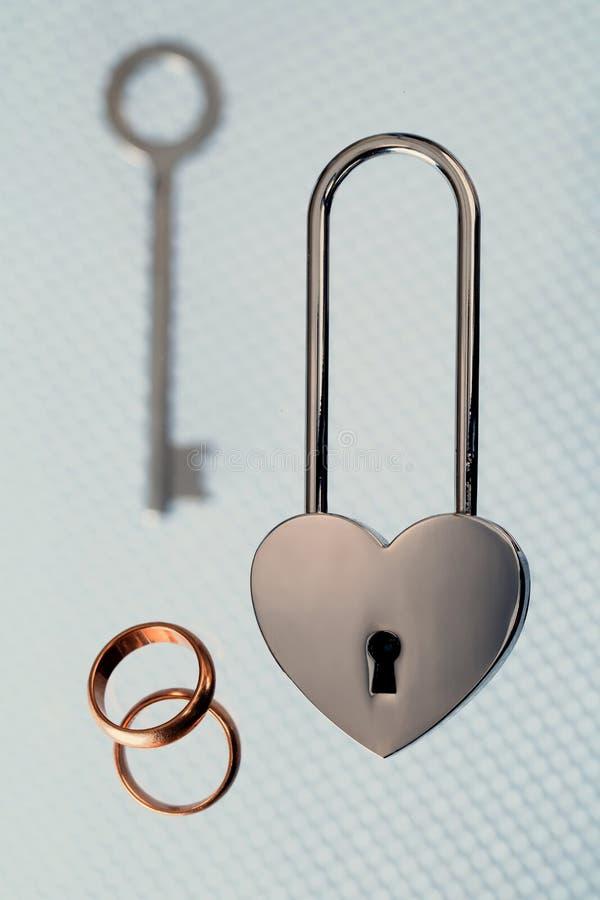 Γαμήλια δαχτυλίδια, κλειδαριά χάλυβα και κλειδί στο ελαφρύ υπόβαθρο στοκ φωτογραφία με δικαίωμα ελεύθερης χρήσης