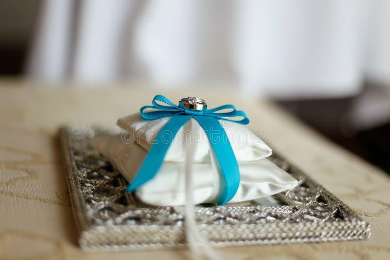 Γαμήλια δαχτυλίδια σε ένα μαξιλάρι με την μπλε κορδέλλα στοκ φωτογραφία με δικαίωμα ελεύθερης χρήσης