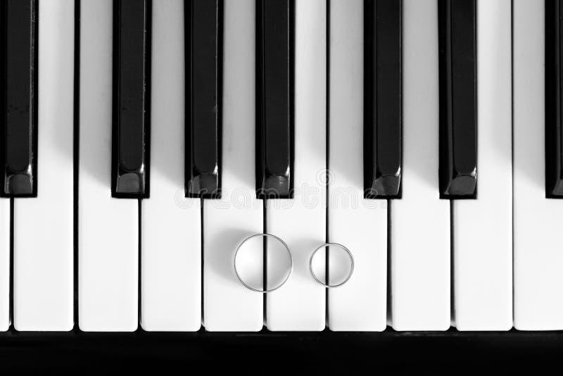 Γαμήλια δαχτυλίδια στη γραπτή κινηματογράφηση σε πρώτο πλάνο πιάνων στοκ φωτογραφία με δικαίωμα ελεύθερης χρήσης
