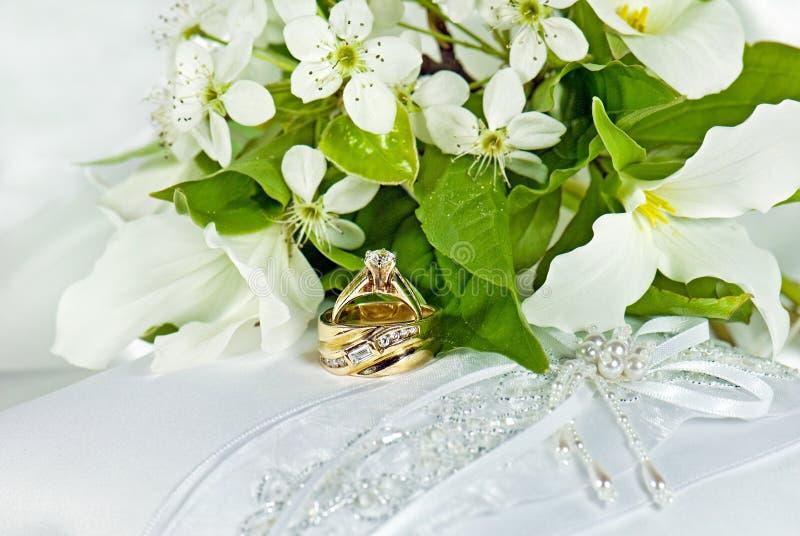 Γαμήλια δαχτυλίδια στο μαξιλάρι σατέν με τα trilliums στοκ φωτογραφία