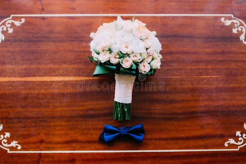 Γαμήλια εξαρτήματα: δεσμός τόξων του νεόνυμφου και της όμορφης νυφικής ανθοδέσμης σε ένα αγροτικό ξύλινο υπόβαθρο στοκ εικόνα