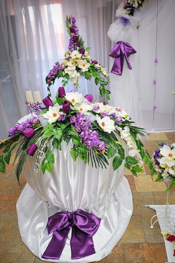 Γαμήλια διακόσμηση στον πορφυρό πίνακα ύφους με τα λουλούδια στοκ εικόνες