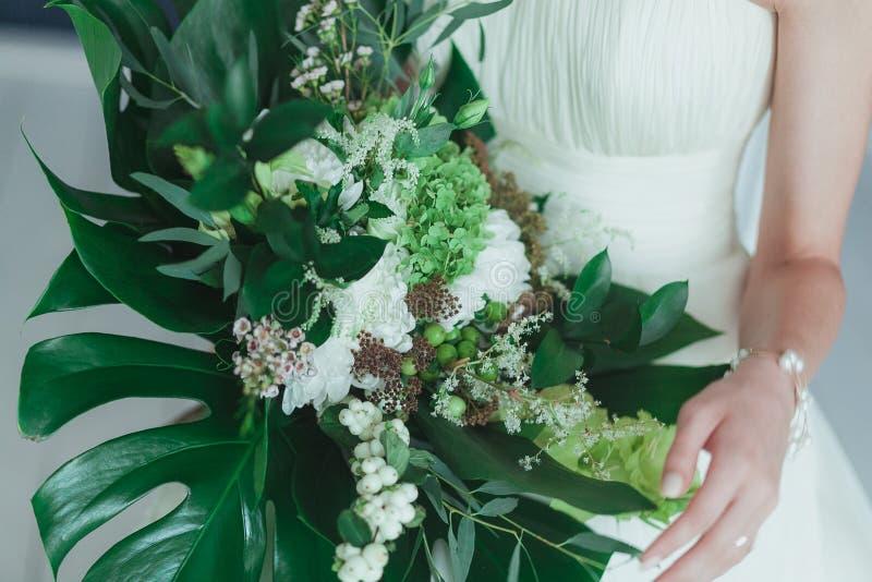 Γαμήλια νυφική ανθοδέσμη με τα μεγάλα τροπικά πράσινα φύλλα και τα άσπρα λουλούδια στοκ φωτογραφία