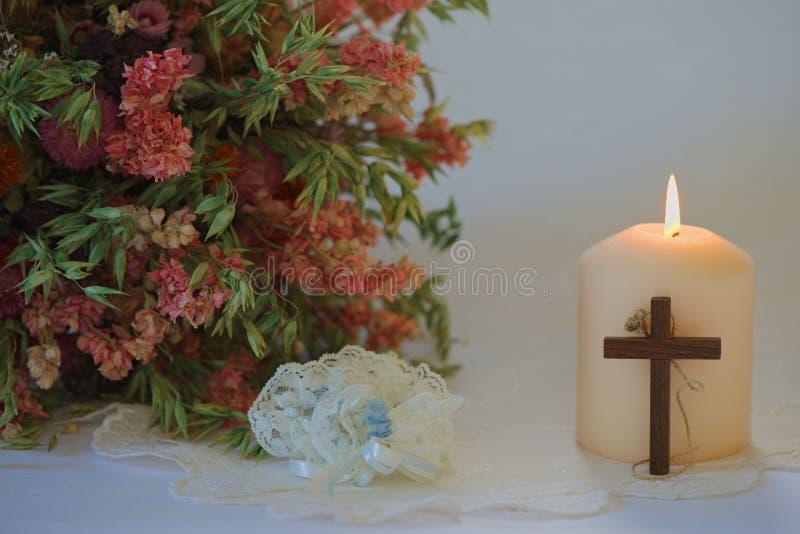 Γαμήλια οργάνωση με τα λουλούδια, το κερί, γαμήλιο garter και το σταυρό στοκ εικόνες με δικαίωμα ελεύθερης χρήσης