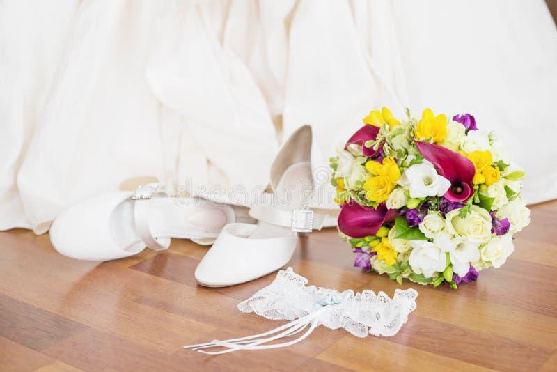 Γαμήλια παπούτσια, garter, και λουλούδια νυφών που κάθονται στο πάτωμα στοκ εικόνες