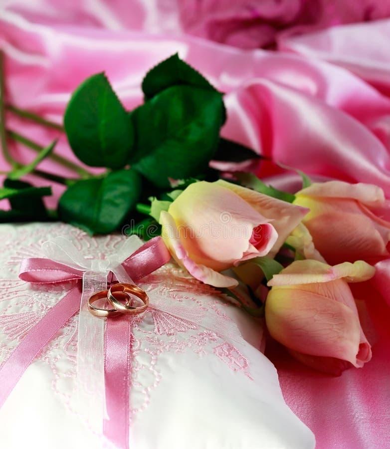 Γαμήλια χρυσά δαχτυλίδια σε ένα μαξιλάρι με τα τριαντάφυλλα στοκ φωτογραφίες
