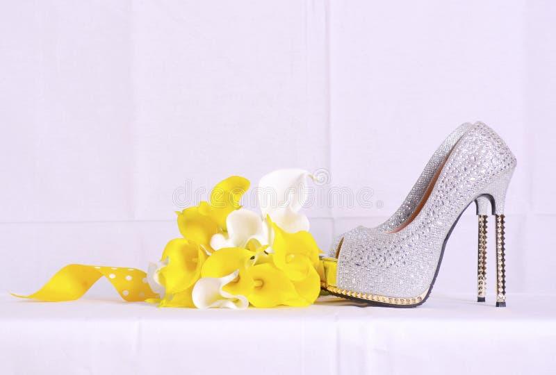 Γαμήλιες παπούτσια και ανθοδέσμη στη φυσική ρύθμιση στοκ φωτογραφία
