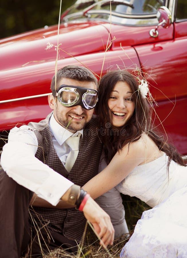 Γαμήλιο αυτοκίνητο με τη νύφη και το νεόνυμφο στοκ εικόνα