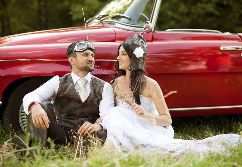 Γαμήλιο αυτοκίνητο με τη νύφη και το νεόνυμφο στοκ εικόνα με δικαίωμα ελεύθερης χρήσης