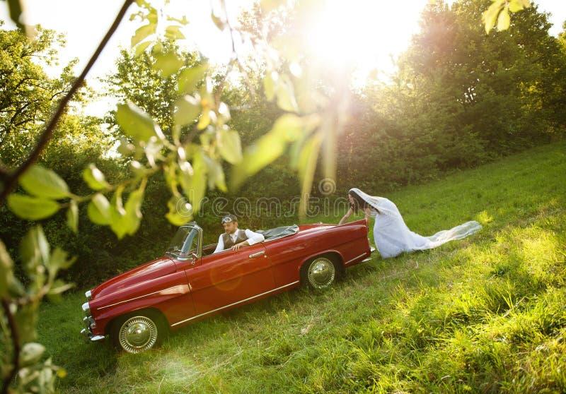 Γαμήλιο αυτοκίνητο με τη νύφη και το νεόνυμφο στοκ φωτογραφία