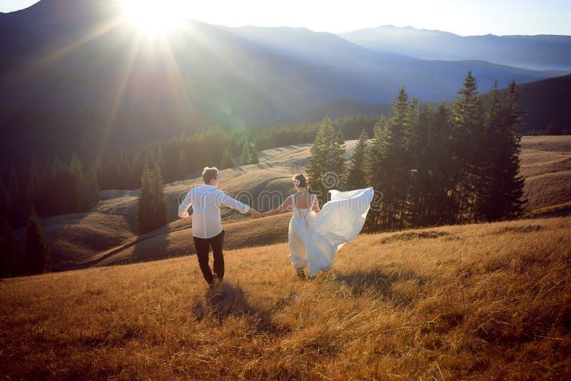 Γαμήλιο ζεύγος που έχει τη διασκέδαση στα βουνά honeymoon στοκ εικόνες