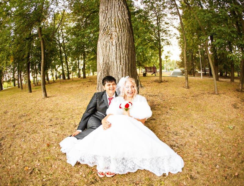Γαμήλιο ζεύγος που αγκαλιάζει, η νύφη που κρατά το α στοκ φωτογραφίες