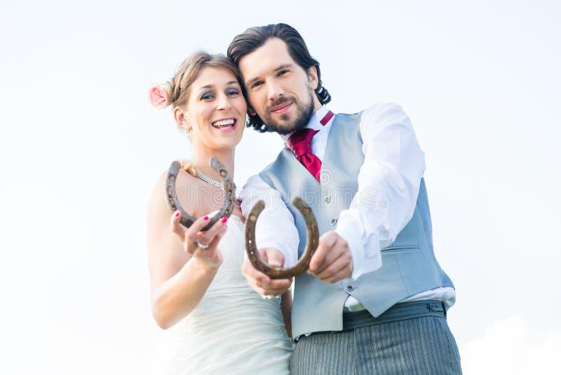 Γαμήλιο ζεύγος που παρουσιάζει παπούτσι αλόγων για την τύχη στοκ φωτογραφίες