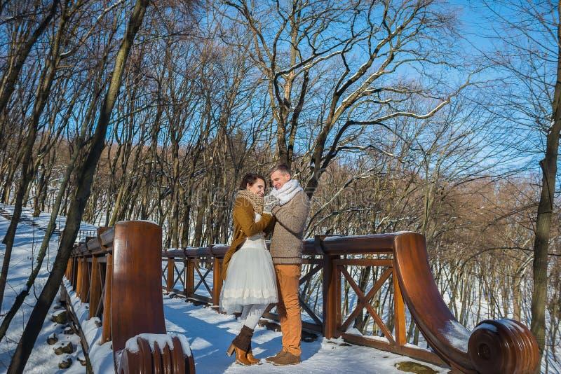 Γαμήλιο ζεύγος σε μια ελκυστική wither ημέρα, που κρατά η μια την άλλη, που στέκεται στη γέφυρα Αγροτικό ύφος Κοντό γαμήλιο φόρεμ στοκ εικόνες