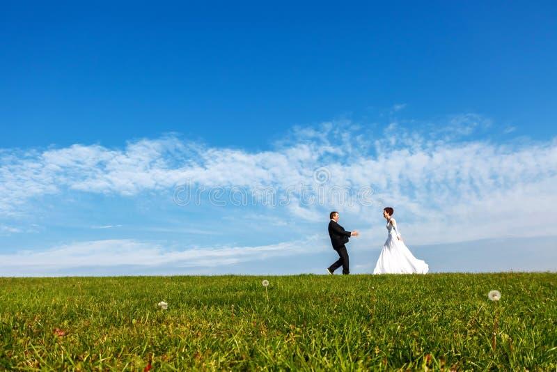 Γαμήλιο ζεύγος υπαίθρια στο υπόβαθρο μπλε ουρανού στοκ εικόνα