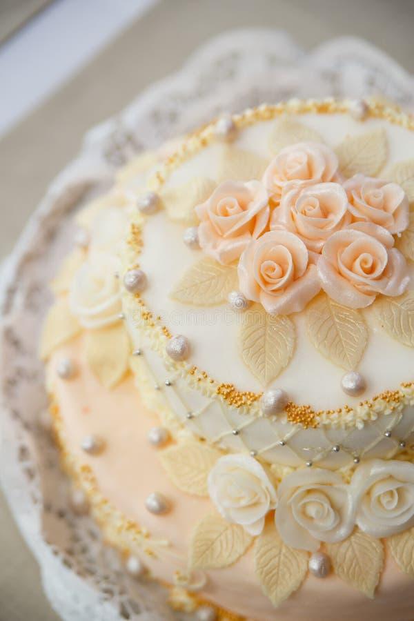 Γαμήλιο κέικ με τα τριαντάφυλλα στην υποδοχή πολυτέλειας στοκ εικόνα με δικαίωμα ελεύθερης χρήσης