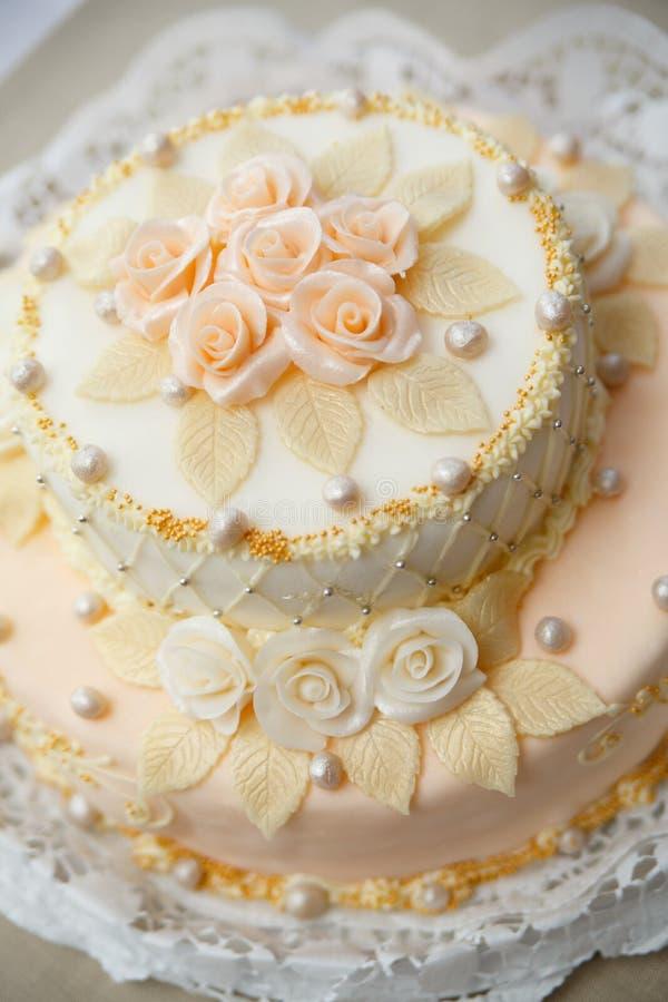 Γαμήλιο κέικ με τα τριαντάφυλλα στην υποδοχή πολυτέλειας στοκ φωτογραφία με δικαίωμα ελεύθερης χρήσης