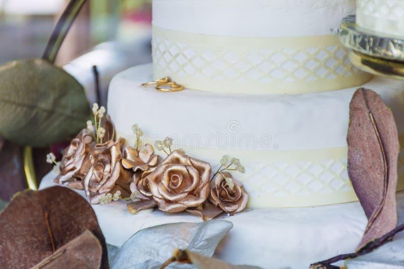 Γαμήλιο κέικ με τα χρυσά τριαντάφυλλα στοκ φωτογραφία