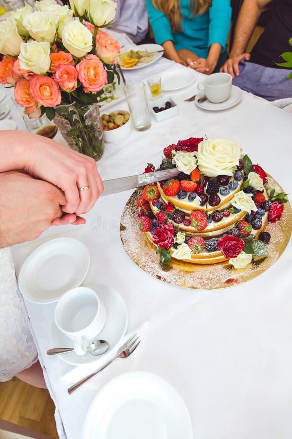 Γαμήλιο κέικ που διακοσμείται από τα φρούτα και τα λουλούδια στοκ φωτογραφία