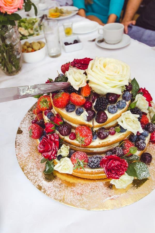 Γαμήλιο κέικ που διακοσμείται από τα φρούτα και τα λουλούδια στοκ εικόνες