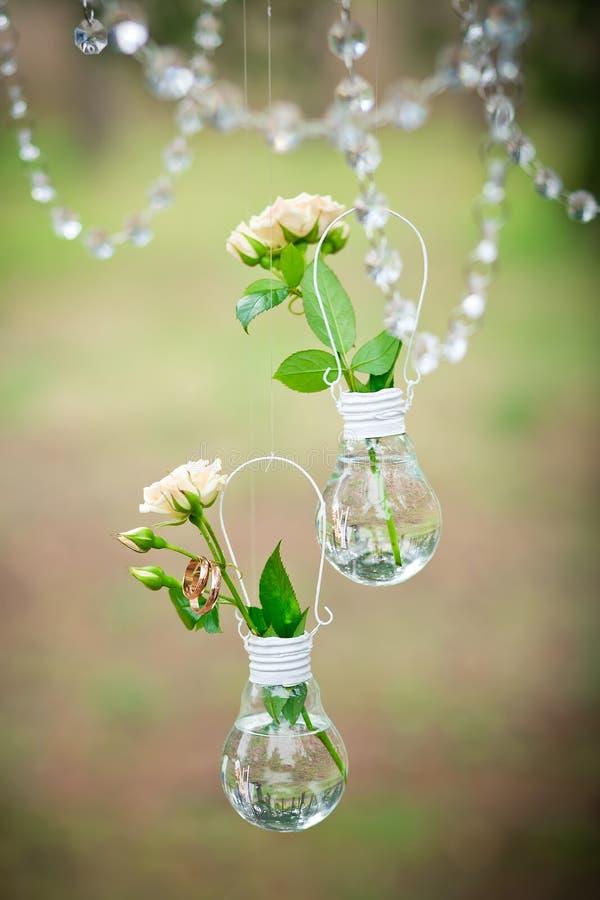 Γαμήλιο ντεκόρ με τα γαμήλια δαχτυλίδια και τα τριαντάφυλλα στους βολβούς στοκ εικόνα με δικαίωμα ελεύθερης χρήσης
