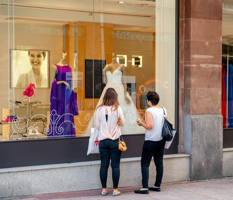 Γαμήλιο φόρεμα αγοράς μητέρων και κορών στο κατάστημα μόδας boutiq στοκ φωτογραφία