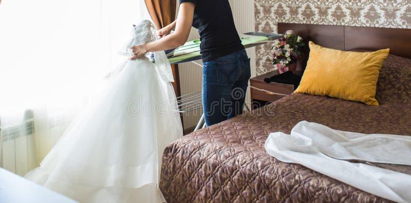 Γαμήλιο φόρεμα σιδερώματος νοικοκυρών στο καθιστικό στοκ φωτογραφία με δικαίωμα ελεύθερης χρήσης