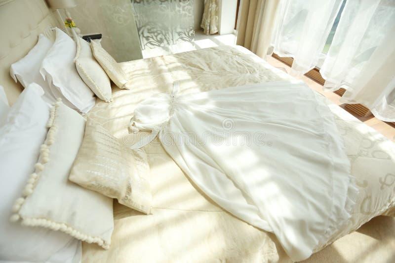 Γαμήλιο φόρεμα στο όμορφο άσπρο κρεβάτι στοκ εικόνα