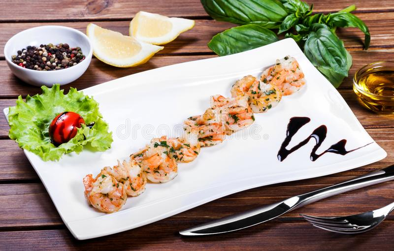 Γαρίδες γαρίδων που ψήνονται με τη σάλτσα και τα πράσινα στο άσπρο πιάτο στον ξύλινο πίνακα στοκ φωτογραφίες με δικαίωμα ελεύθερης χρήσης