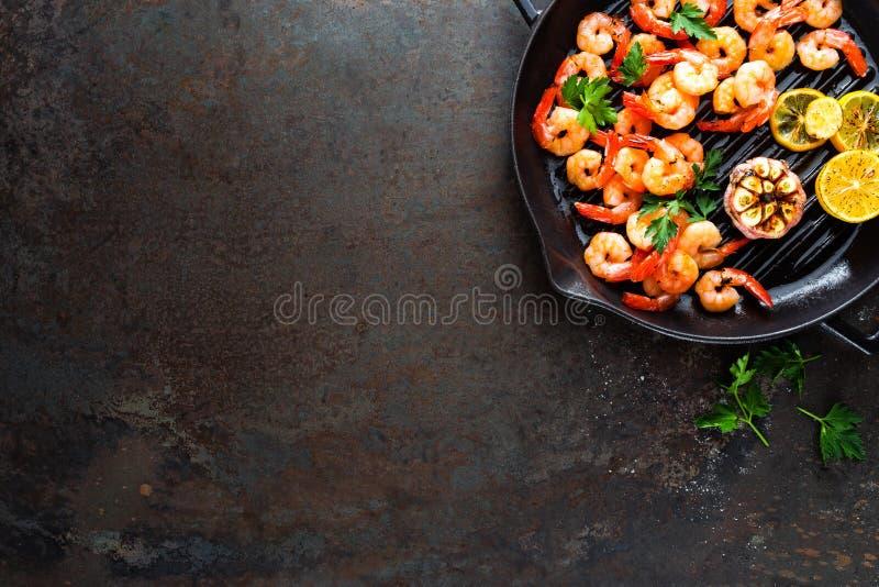Γαρίδες που ψήνονται στο τηγανίζοντας τηγάνι σχαρών με το λεμόνι και το σκόρδο Ψημένες στη σχάρα γαρίδες, γαρίδες Θαλασσινά Τοπ ό στοκ εικόνες