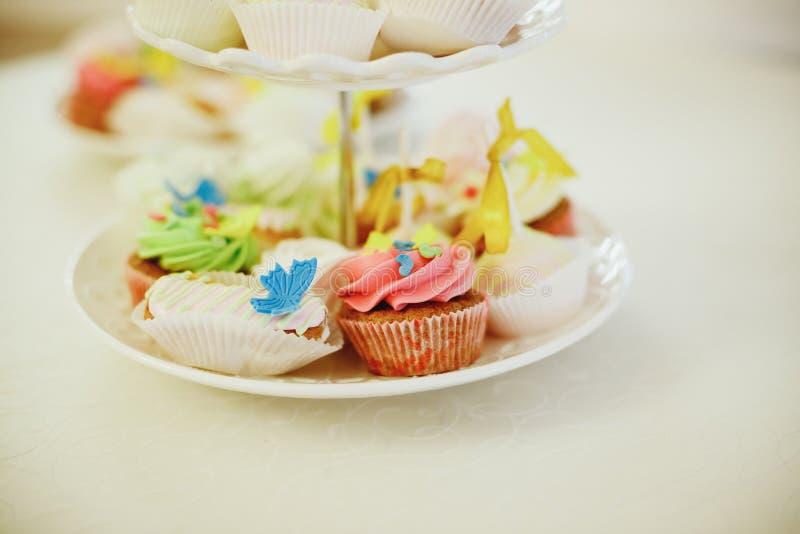 Γαστρονομικά cupcakes με το ζωηρόχρωμο buttercream που παγώνει στον άσπρο πίνακα εικόνα διακοπών, εορταστικό αρτοποιείο εικόνα πο στοκ εικόνα