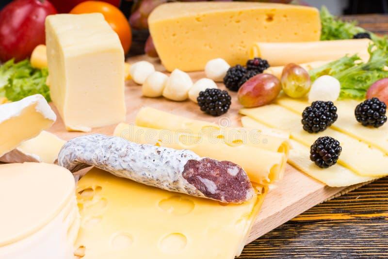 Γαστρονομικός πίνακας τυριών με το θεραπευμένα κρέας και τα φρούτα στοκ φωτογραφία με δικαίωμα ελεύθερης χρήσης