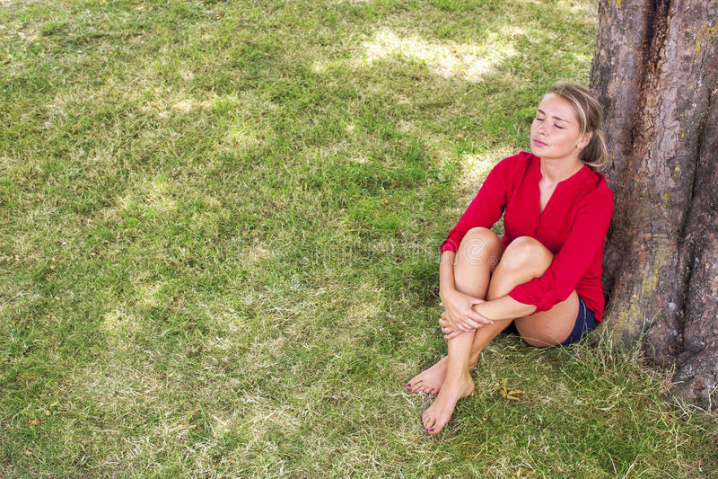 Γαλήνια νέα γυναίκα που απολαμβάνει τη θερινή φρεσκάδα κάτω από ένα δέντρο στοκ εικόνες