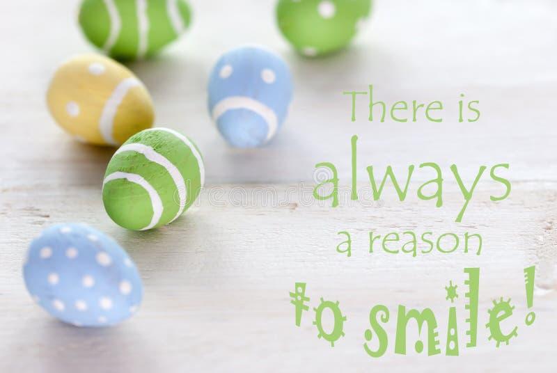 Γαλαζοπράσινα και κίτρινα αυγά Πάσχας με το απόσπασμα ζωής υπάρχει πάντα ένας λόγος να χαμογελάσει στοκ εικόνες με δικαίωμα ελεύθερης χρήσης