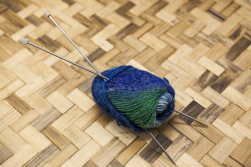 Γαλαζοπράσινες σφαίρες του νήματος για το πλέξιμο με τα spokes στο α σε ένα ξύλινο υπόβαθρο στοκ εικόνες