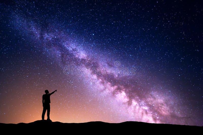 Γαλακτώδης τρόπος με τη σκιαγραφία ενός μόνιμου ατόμου που δείχνει το δάχτυλο στον έναστρο ουρανό νύχτας στοκ φωτογραφίες