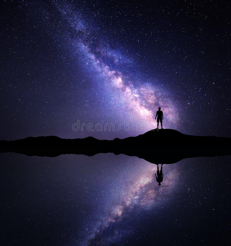 Γαλακτώδης τρόπος Σκιαγραφία ενός μόνιμου ατόμου κοντά στη λίμνη στοκ φωτογραφίες με δικαίωμα ελεύθερης χρήσης