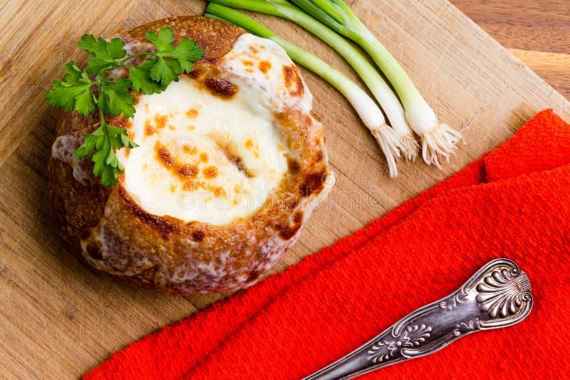 Γαλλική σούπα κρεμμυδιών που εξυπηρετείται σε ένα κύπελλο ψωμιού στοκ εικόνες με δικαίωμα ελεύθερης χρήσης