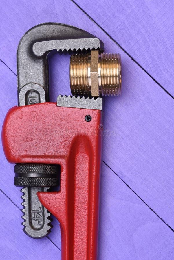 Γαλλικό κλειδί εργαλείων εργασίας και μέρος υδραυλικών ορείχαλκου στοκ φωτογραφία με δικαίωμα ελεύθερης χρήσης