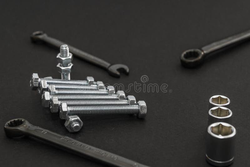 Γαλλικό κλειδί, καρύδια - και - μπουλόνια σε ένα γκρίζο υπόβαθρο στοιχεία για να τοποθετήσει τις λεπτομέρειες στοκ φωτογραφίες με δικαίωμα ελεύθερης χρήσης