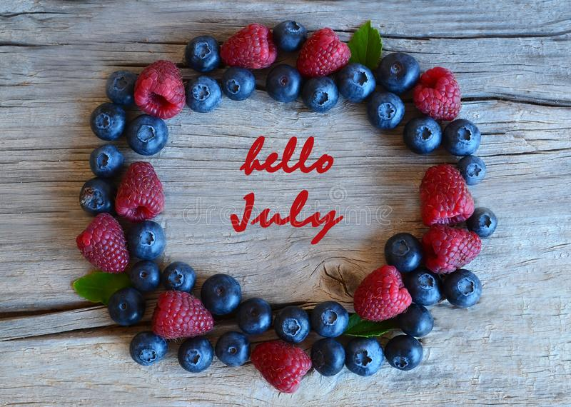 Γειά σου ευχετήρια κάρτα Ιουλίου με το κείμενο με με τα φρέσκα ώριμα μούρα στο παλαιό ξύλινο υπόβαθρο Βακκίνιο και σμέουρο Καλοκα στοκ εικόνες