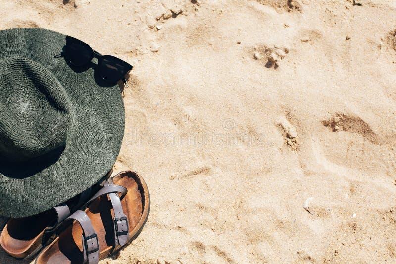 Γειά σου θερινή έννοια Μοντέρνες καπέλο, γυαλιά ηλίου και παντόφλες στην αμμώδη παραλία Εξάρτημα κοριτσιών στην παραλία Οι θερινέ στοκ φωτογραφία με δικαίωμα ελεύθερης χρήσης
