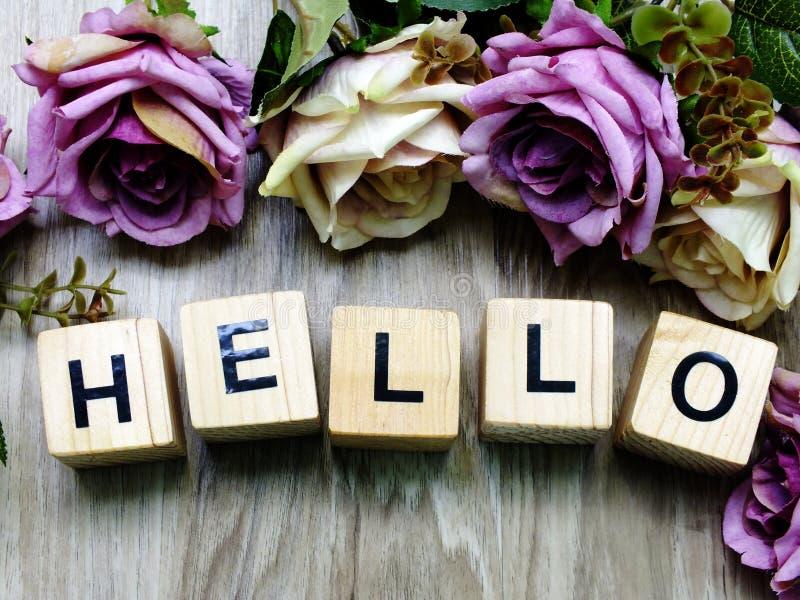 Γειά σου ξύλινος φραγμός λέξης με το τεχνητό ντεκόρ λουλουδιών τριαντάφυλλων στοκ εικόνες