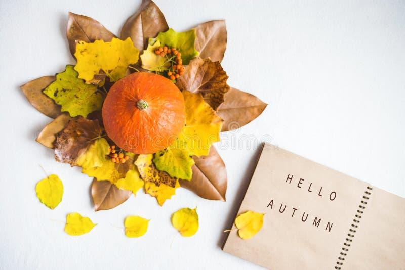 Γειά σου, φθινόπωρο Το πορτοκαλί φύλλωμα φθινοπώρου σημειωματάριων κολοκυθών σε ένα ξύλινο επίπεδο υποβάθρου βρέθηκε στοκ φωτογραφίες