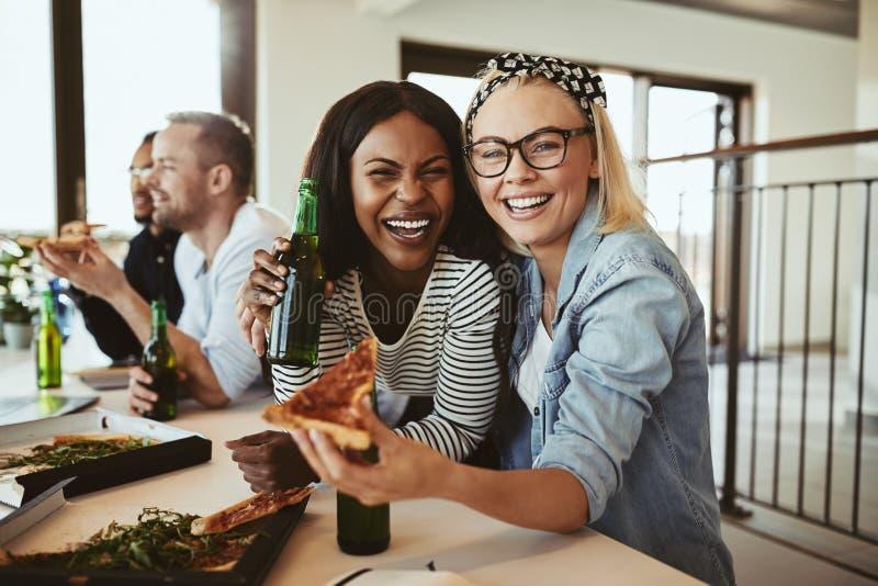 Γελούσες επιχειρηματίες που έχουν μπύρες και πίτσα με συναδέλφους στοκ εικόνα