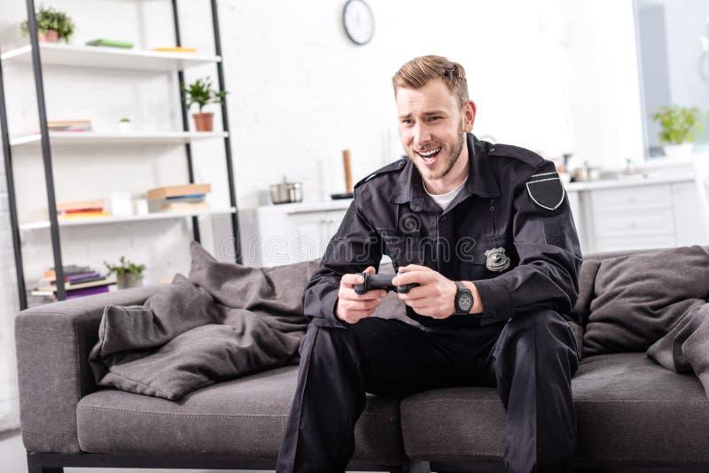 γελώντας αστυνομικός με τη συνεδρίαση gamepad στον καναπέ και στοκ εικόνες με δικαίωμα ελεύθερης χρήσης