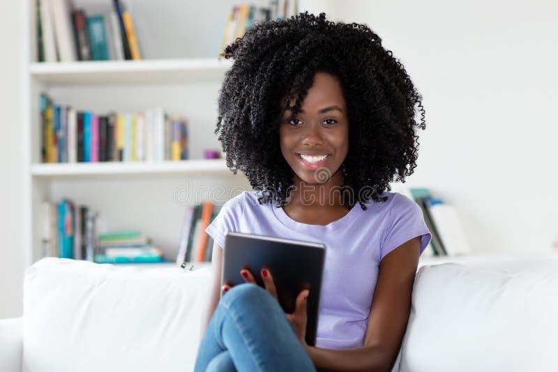 Γελώντας γυναίκα αφροαμερικάνων με τον υπολογιστή ταμπλετών στοκ φωτογραφίες