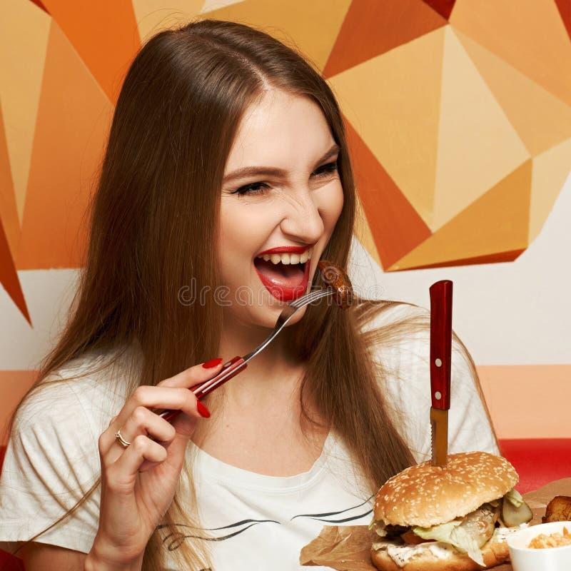 Γελώντας γυναίκα που τρώει burger στοκ φωτογραφία