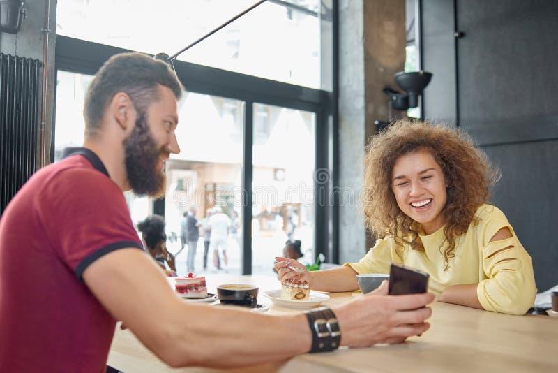 Γελώντας ζεύγος που τρώει το κέικ, πίνοντας τον καφέ, που εξετάζει το smartphone στοκ εικόνες